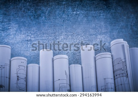 Vintage scratched shiny silver-metal background with rolled blueprints horizontal view construction concept. - stock photo