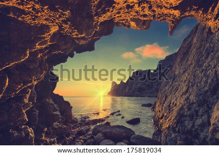 Vintage sea sunset from the mountain cave - stock photo