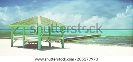 Vintage seascape of Caribbean white sand beach with beach hut, turquoise sea and clouds in the background, panoramic view - stock photo