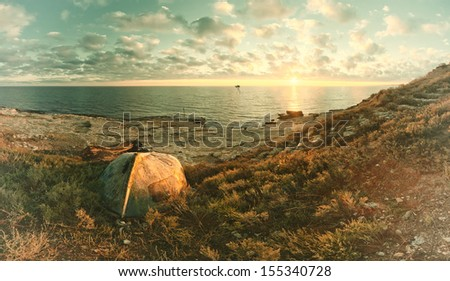 Vintage seascape on sunrise with old boat on coast and clouds in sky - stock photo