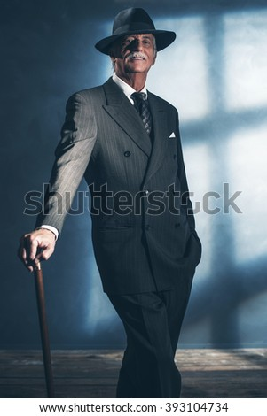 Vintage 1940 senior businessman standing with cane in room. - stock photo