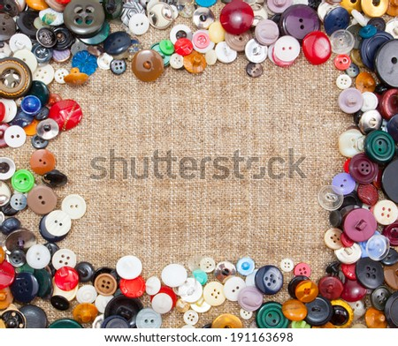 Vintage Sewing Buttons Framing Fabric Background - stock photo