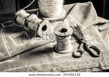 Vintage sewing table with threads, needle and scissors - stock photo