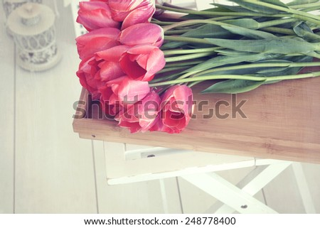 Vintage shabby chic photo of bouquet of spring tulips on a wooden tray on white wooden floor - stock photo