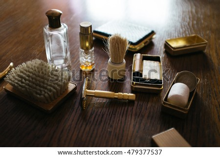 Vintage shaving kit for man and cosmetics. Retro shaver, brush and perfume bottle on a wooden table.