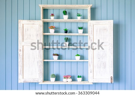 vintage shelf decoration with plant in pot - stock photo