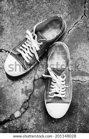 vintage shoes on crack pathway, crack stone / explorer and adventure concept / B&W film processed