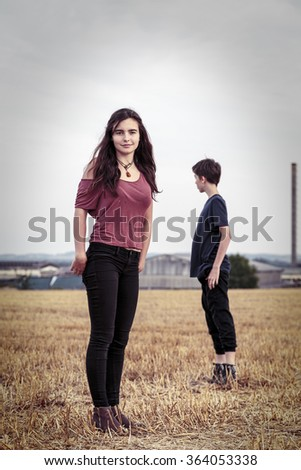 vintage shot of two teenager on a harvested field - stock photo
