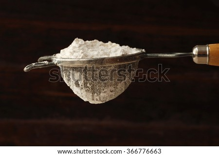 Vintage sieve filled with flour against rustic wood background.  Baking concept/ background.