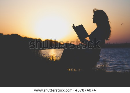 Vintage silhouette of a young beautiful woman at dawn sitting on a folding chair and think about the information which is read