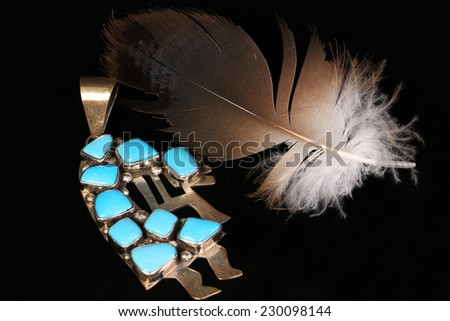 Vintage Silver and turquoise Native American fertility deity, Kokopelli, on black background with feather.  Still life with copy space - stock photo