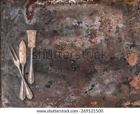 Vintage silver cutlery on rustic textured metal background. Antique tableware - stock photo
