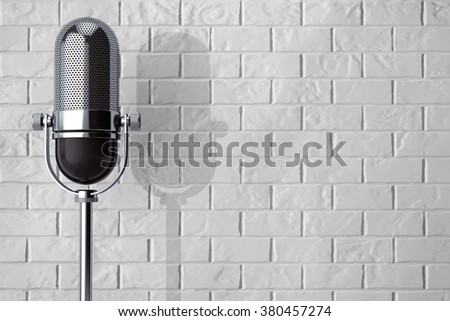 Vintage silver microphone in front of brick wall - stock photo