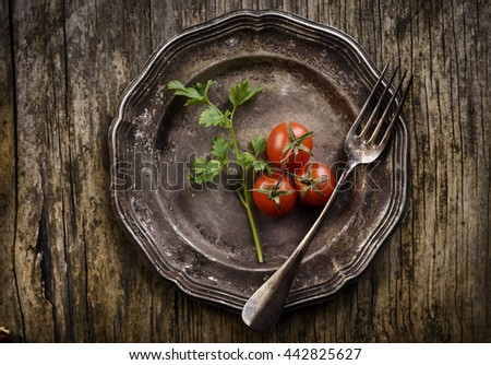Vintage silver plate and fork on aged wooden background
