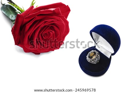 Vintage silver ring in a box and red rose on white background - stock photo