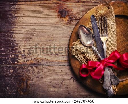 Vintage silverware decorated with red ribbon - stock photo