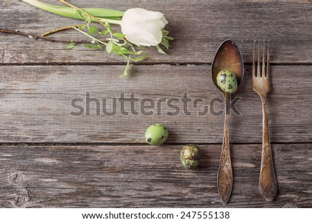 vintage silverware fork and spoon with easter eggs on old wooden table - stock photo