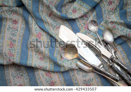 Vintage silverware on classic old fabric. Classic background