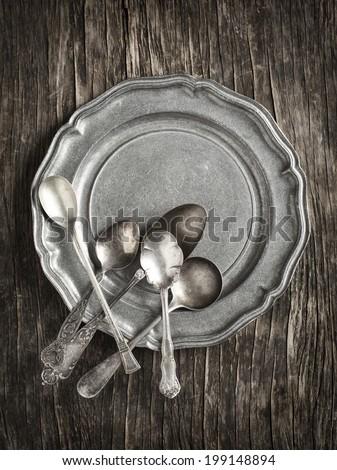 Vintage silverware on rustic metal plate - stock photo