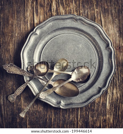 Vintage silverware on rustic metal plate - stock photo