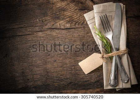 Vintage silverware with a twig of rosemary and empty tag on rustic wooden background - stock photo