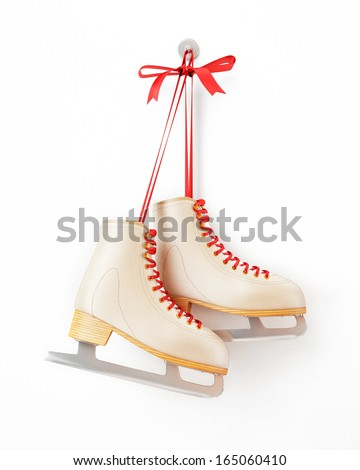 vintage skates hanging on the white wall, isolated on white background - stock photo