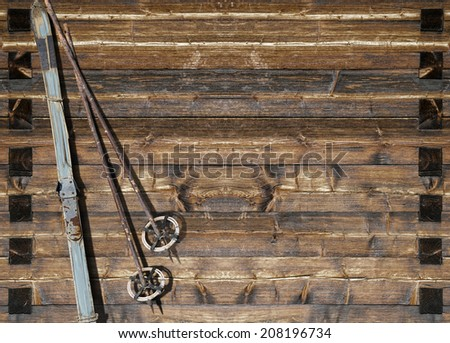 Vintage ski  with poles fixed on a wooden wall. Variant with flaked off  blue color. - stock photo