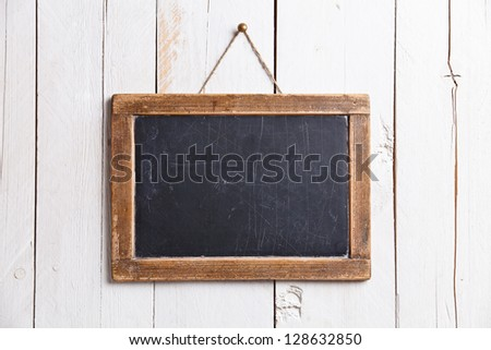Vintage slate chalk board hanging on wooden background - stock photo