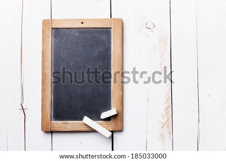 Vintage slate chalk board with chalk on white wooden background - stock photo