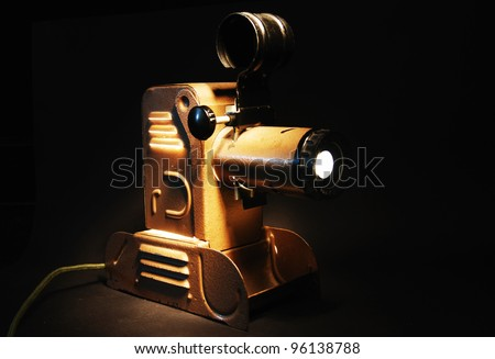 vintage slide projector with the light in dark room - stock photo