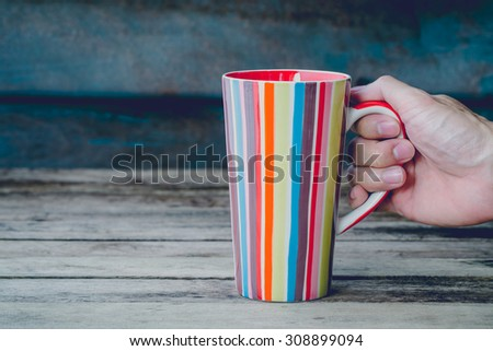 vintage soft tone with hand hold colorful mug. - stock photo