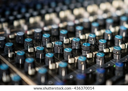 Vintage sound or audio mixer in a recording studio. Knobs, dials and sliders on a soundboard. - stock photo