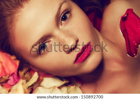 Vintage spa concept. Portrait of a fashionable red-haired (ginger) model with sexy pink lips lying on fading rose petals background. Freckle face. Retro style. Close up. Studio shot - stock photo