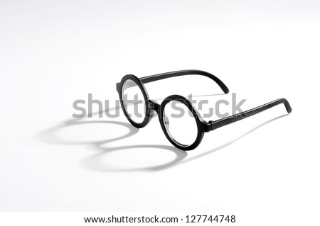 Vintage spectacles with round lenses on a white background casting an interesting shadow with copy space - stock photo