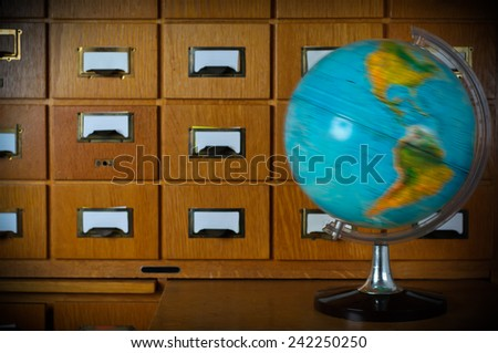 Vintage Spinning Globe in Front of Old Library Card Catalog Stock Photo - stock photo