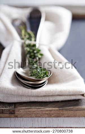 Vintage spoons and thyme sprig on a napkin creative selective focus - stock photo