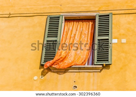 vintage square window with green shutters and orange curtain on deep yellow wall - stock photo