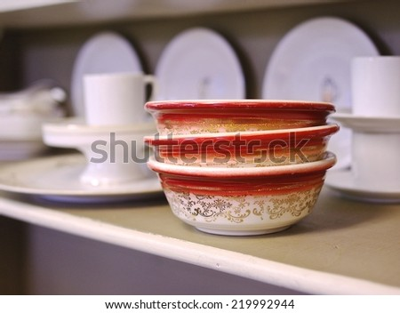 Vintage Stack of Bowls: close up of three orange & white bowls with a gold flowered pattern, stacked three high resting on a shelf amongst a backdrop of assorted white dishes at a thrift store. - stock photo