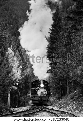 Vintage steam engine pulls a train uphill in Colorado.