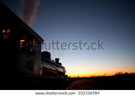 Vintage steam locomotive pointed into the sunset - stock photo