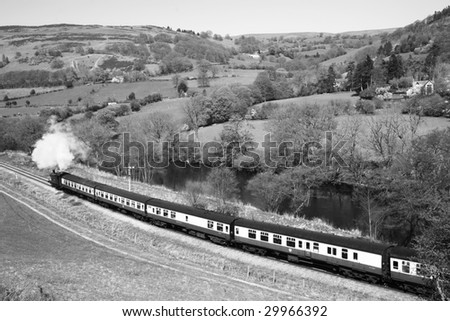 vintage steam train passing through countryside in black and white - stock photo