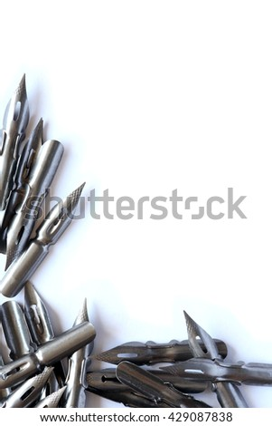 Vintage steel nib set as border on white paper background - stock photo