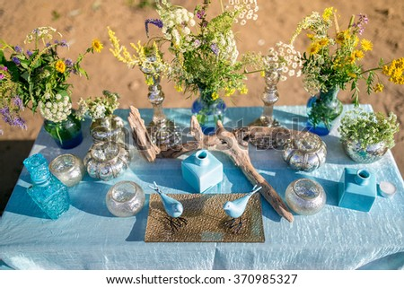 Vintage still life: Adorned designer table with vase of flowers and decor in turquoise and blue style. Outdoor decor composition