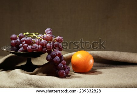 Vintage still life. Bunch of red grapes in metal bowl near orange on canvas background - stock photo
