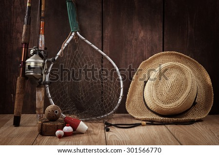 Vintage still life. Fishing poles, bobbers, hat and net.  Focus on Bobbers in foreground.  - stock photo