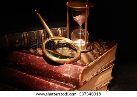 Vintage still life. Magnifying glass and hourglass near old books