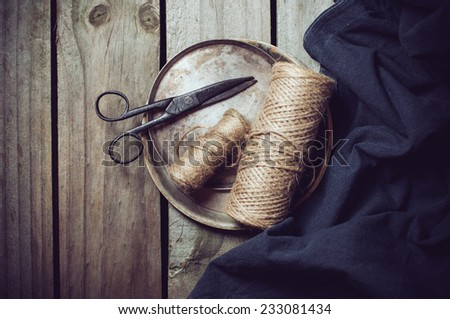 Vintage still life, old scissors, cupronickel trays, dark cloth and a few skeins of rough rope on a wooden board - stock photo