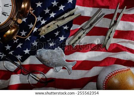 vintage still life, the American flag, an old alarm clock, glasses, baseball, clothespins, fish - stock photo