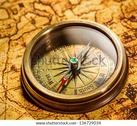 Vintage still life. Vintage compass lies on an ancient world map. - stock photo