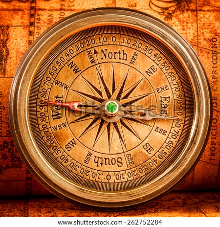 Vintage still life. Vintage compass lies on an ancient world map in 1565. - stock photo